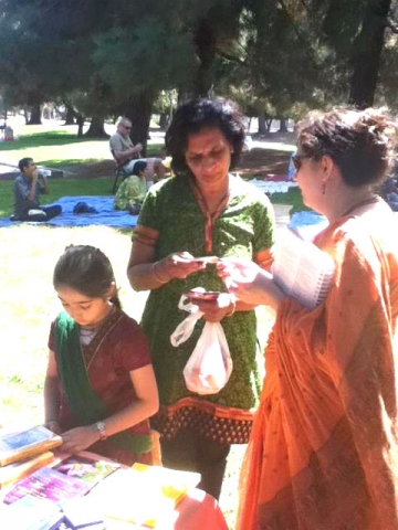 janmastami-ponderosa-park-03 Abha Devi Dasi shares information about our community with a guest while her daughter Lavanika organizes the book table